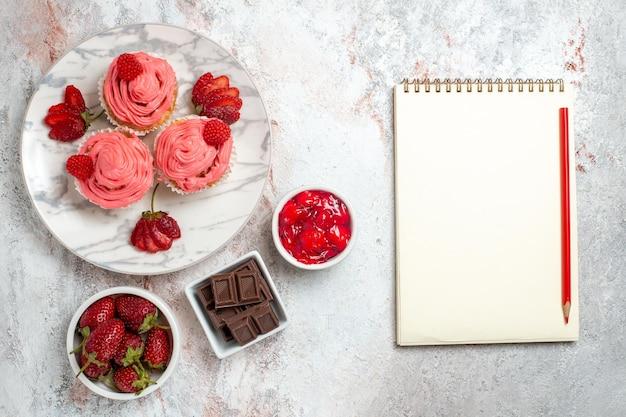 Bovenaanzicht van roze aardbeientaarten met jam en chocoladerepen op witte ondergrond