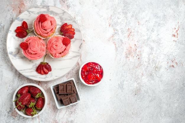 Bovenaanzicht van roze aardbeientaarten met jam op witte ondergrond