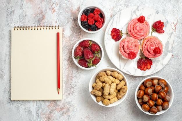 Bovenaanzicht van roze aardbeientaarten met noten op witte ondergrond