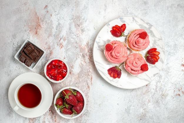 Bovenaanzicht van roze aardbeientaarten met slagroom en kopje thee op witte ondergrond