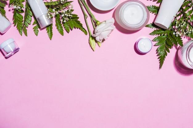 Bovenaanzicht van roze achtergrond met cosmetische producten.