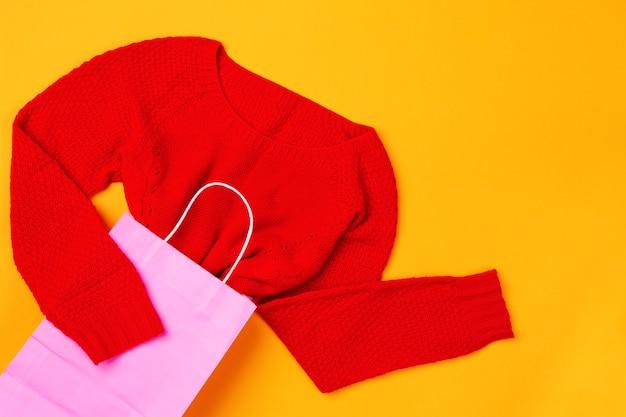 Bovenaanzicht van roze boodschappentas met rode trui. concept van mode en design, winkelen