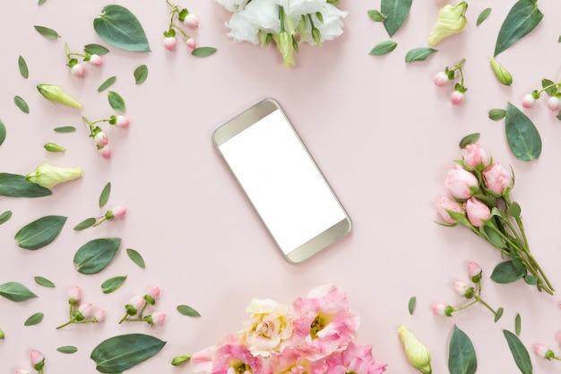 Bovenaanzicht van roze bureau met moderne gouden mobiele telefoon en bloem frame
