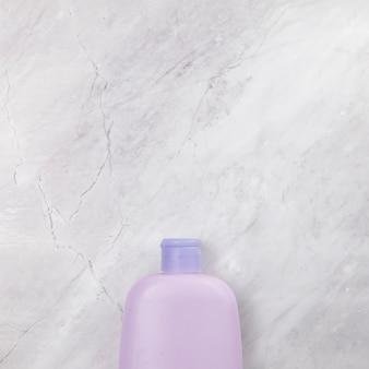 Bovenaanzicht van roze fles op marmeren achtergrond
