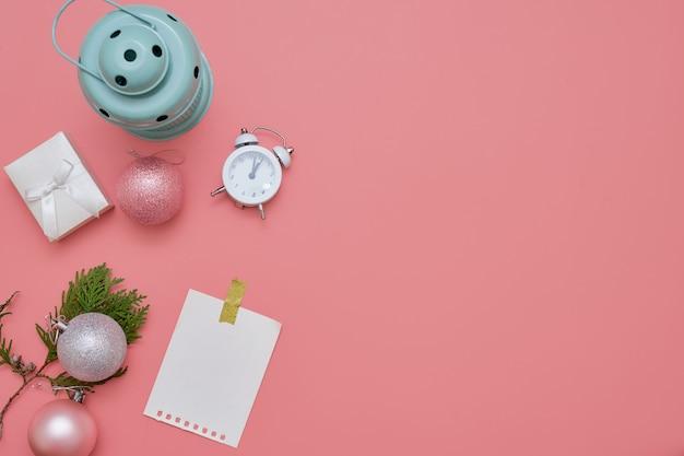 Bovenaanzicht van roze kerstballen en mint lamp op roze achtergrond