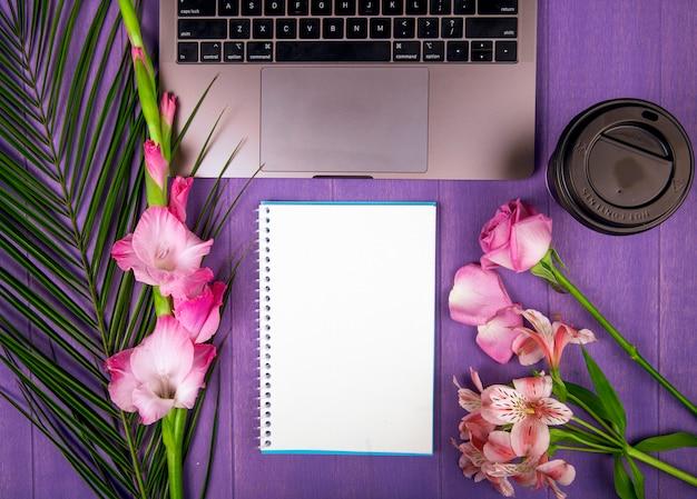 Bovenaanzicht van roze kleur gladiolen en rozen met alstroemeria bloemen gerangschikt rond een schetsboek laptop en een papieren kopje koffie op paarse achtergrond