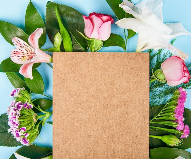 Bovenaanzicht van roze kleur rozen en alstroemeria bloemen met turkse anjer met een bruin vel papier op blauwe achtergrond