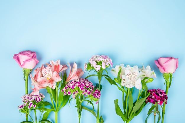 Bovenaanzicht van roze kleur rozen en alstroemeria bloemen met turkse anjer op blauwe achtergrond met kopie ruimte