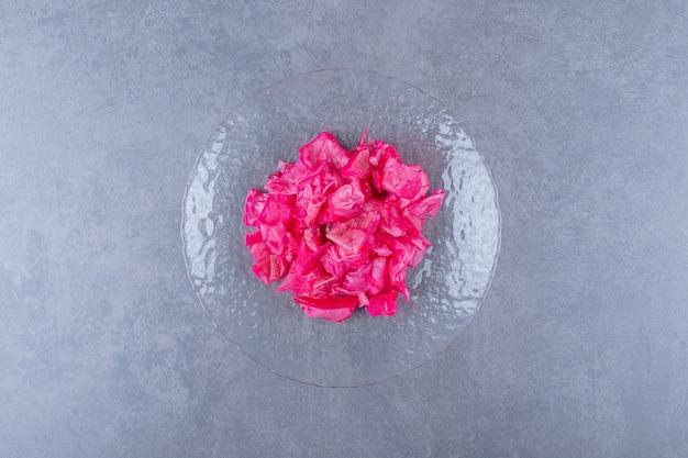 Bovenaanzicht van roze kool in blik op glasplaat.