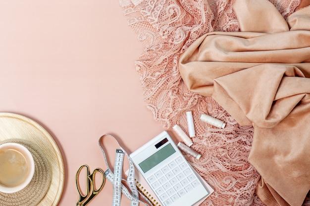 Bovenaanzicht van roze koraal gekleurde kant en zijden stoffen met draadspoelen, rekenmachine op kladblok, meetlint, schaar in de buurt van kopje koffie op roze achtergrond. avondjurken naaien concept.
