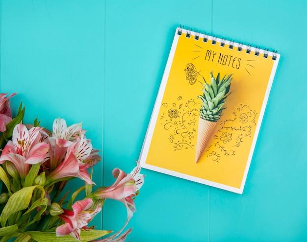 Bovenaanzicht van roze lelies met een notitieboekje op een blauwe ondergrond