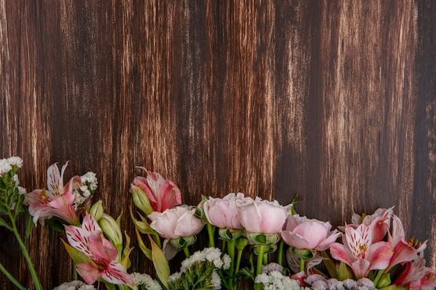 Bovenaanzicht van roze lelies met roze rozen op een houten oppervlak