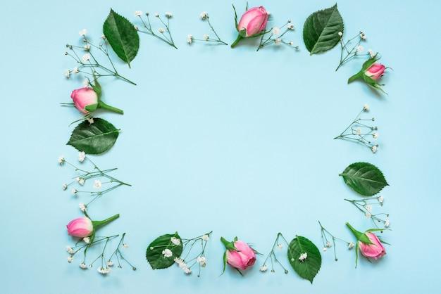 Bovenaanzicht van roze rozen en groene bladeren krans gerangschikt in vierkant op blauwe achtergrond. abstract floral achtergrond.