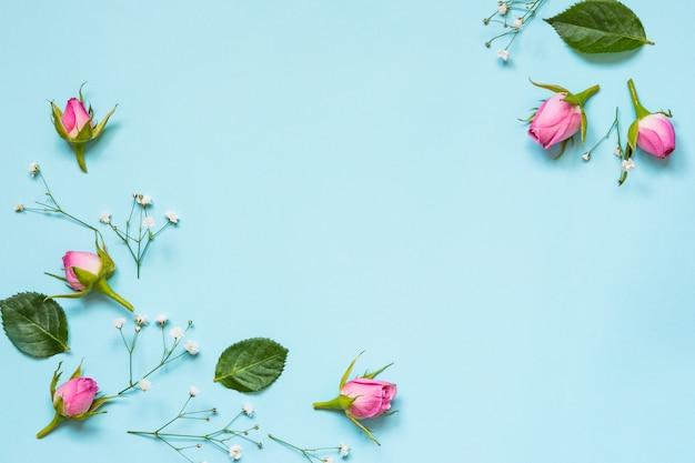 Bovenaanzicht van roze rozen en groene bladeren op blauwe achtergrond. abstract floral achtergrond. kopieer ruimte.