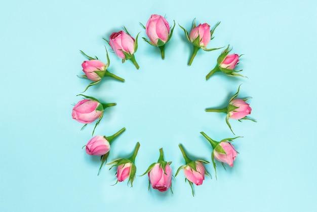 Bovenaanzicht van roze rozen gerangschikt in cirkel op blauwe achtergrond. abstract floral achtergrond.