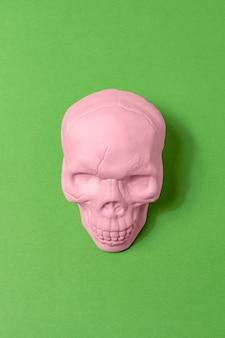 Bovenaanzicht van roze schedel op groene achtergrond