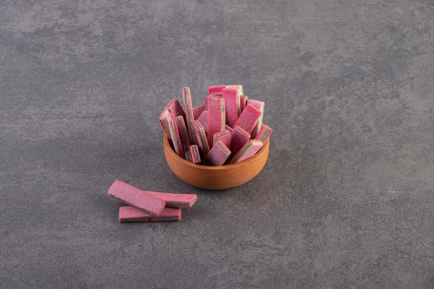 Bovenaanzicht van roze tandvlees in kom over grijs oppervlak