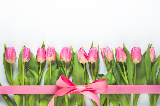 Bovenaanzicht van roze tulpen gerangschikt in lijn, omwikkeld met roze lint op witte achtergrond.