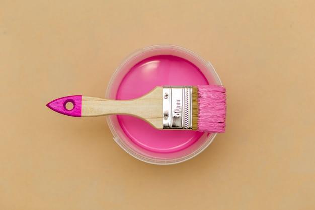 Bovenaanzicht van roze verf en penseel