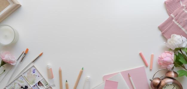 Bovenaanzicht van roze vrouwelijke kunstenaar werkruimte met kopie ruimte en tekengereedschappen