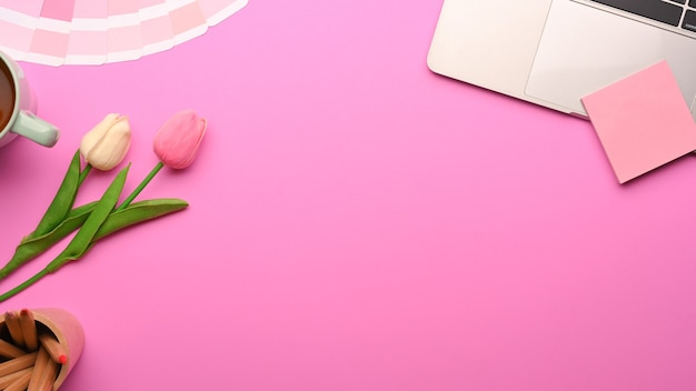 Bovenaanzicht van roze vrouwelijke plat lag werkruimte met laptop, kladblok, verfgereedschap, tulpenbloemen en kopieerruimte