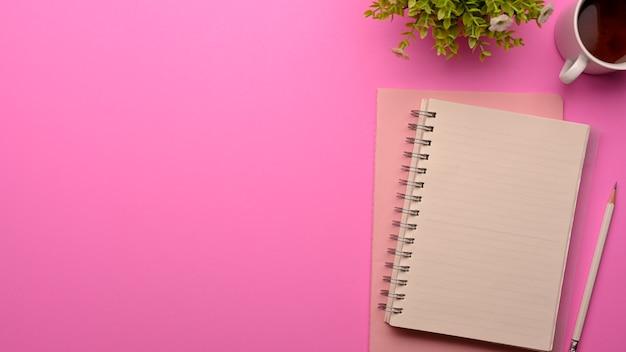 Bovenaanzicht van roze vrouwelijke werkruimte met notitieboekjes, potlood, mok, plantpot en kopieerruimte