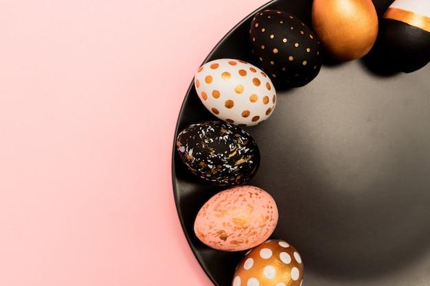 Bovenaanzicht van roze, witte en gouden versierde paaseieren op zwarte plaat op roze achtergrond. trendy vakantieachtergrond