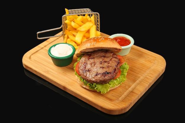 Bovenaanzicht van runderburger en tomaat en sla met frietjes met mayonaise en ketchup