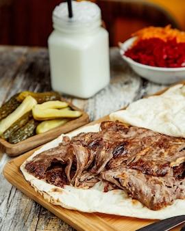 Bovenaanzicht van rundvlees doner plakjes geplaatst tussen flatbread