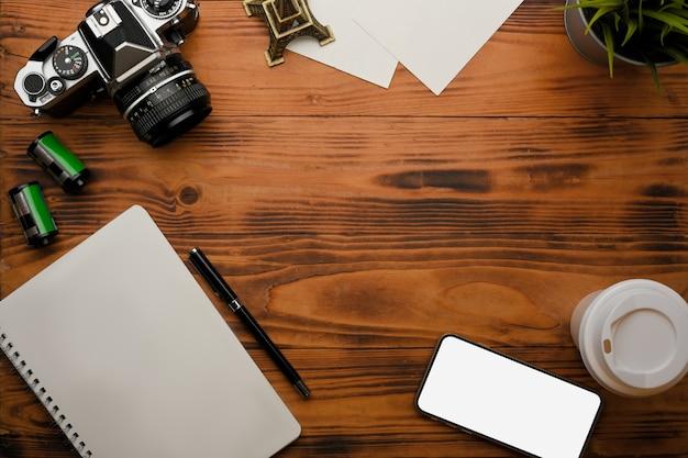 Bovenaanzicht van rustieke tafel met camera-benodigdheden voor smartphone-briefpapier en kopie ruimte