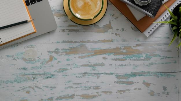 Bovenaanzicht van rustieke werkplek met laptop, camera, kantoorbenodigdheden, koffiekopje en kopie ruimte