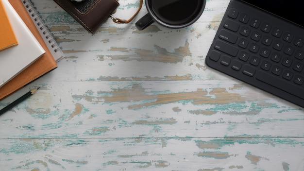 Bovenaanzicht van rustieke werkplek met tablet, camera, kantoorbenodigdheden en kopie ruimte