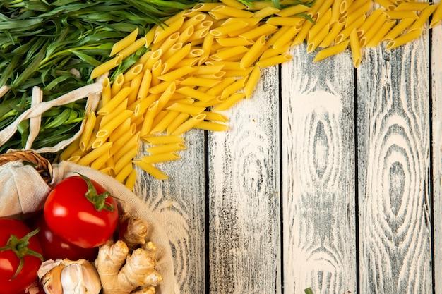 Bovenaanzicht van ruwe penne rigate pasta dragon en tomaten met kopie ruimte