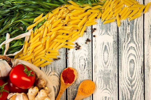 Bovenaanzicht van ruwe penne rigate pasta dragon houten lepel met kruiden een mand met tomaten en gember met kopie ruimte