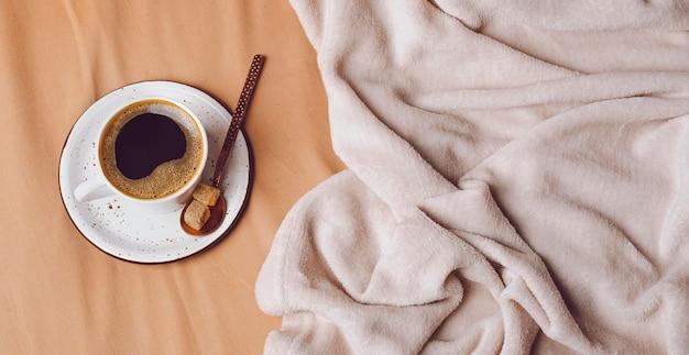 Bovenaanzicht van 's ochtends koffiekopje op bed met kopie ruimte