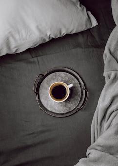 Bovenaanzicht van 's ochtends koffiekopje op bed