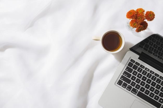 Bovenaanzicht van 's ochtends thee in voile stof achtergrond met een laptop, mok thee en een vaas met oranje bloemen met ruimte voor tekst