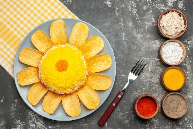 Bovenaanzicht van salade aan de linkerkant midden met geel servet eronder en vork en kruiden aan de zijkant op donkergrijze achtergrond