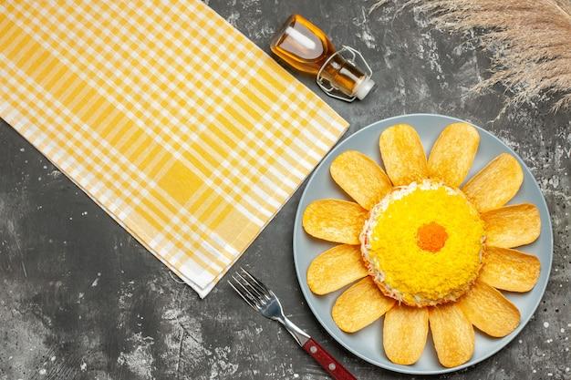 Bovenaanzicht van salade aan de rechterkant met gele servet oliefles vork en tarwe aan de zijkant op donkergrijze tafel