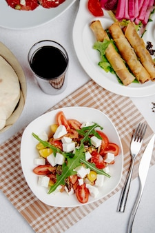 Bovenaanzicht van salade met fetakaas en tomaten op tafel