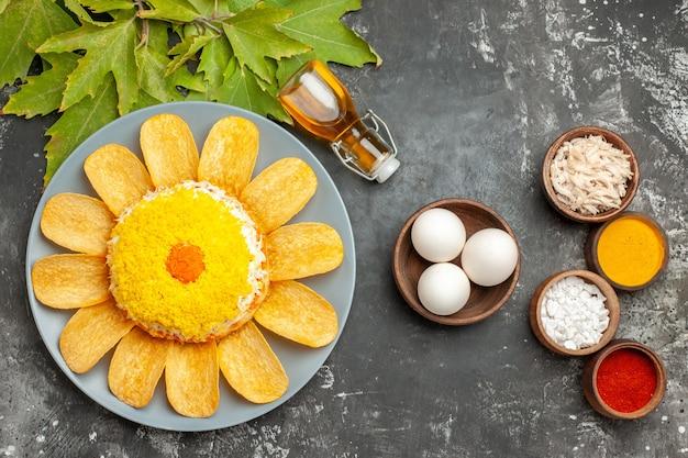 Bovenaanzicht van salade met oliefles kom met eieren en bladeren aan de zijkant met kruiden ernaast op donkergrijze tafel