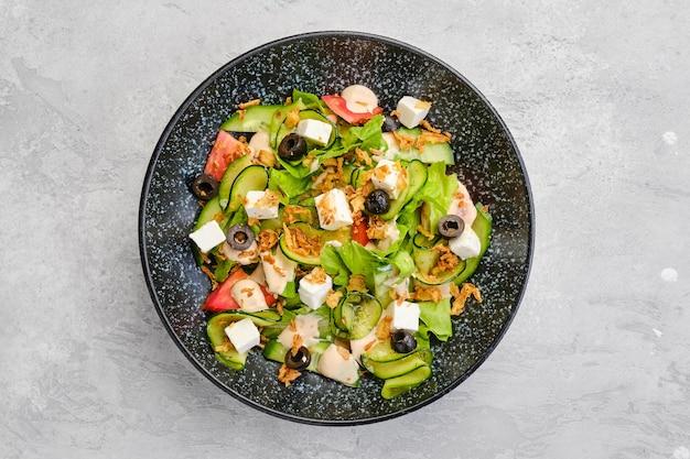 Bovenaanzicht van salade met sla, komkommer, olijven, tomaat, fetakaas en baconchips