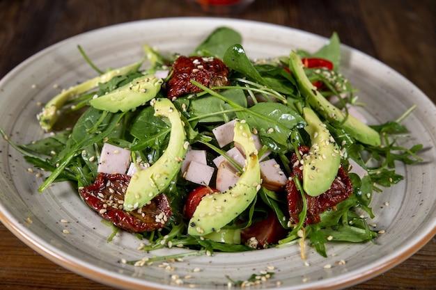 Bovenaanzicht van salade met tomaten, zongedroogde tomaten, avocado, spinazie, kalkoen en sesam