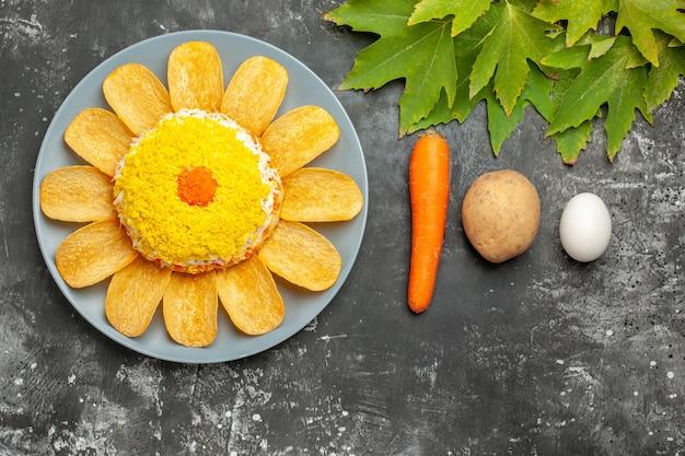 Bovenaanzicht van salade met wortelaardappel en ei en bladeren op donkere achtergrond