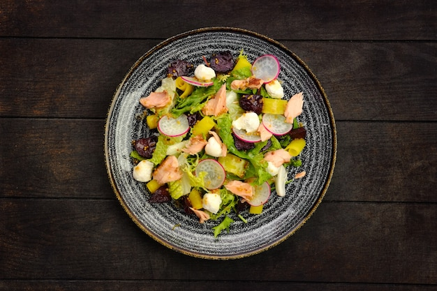 Bovenaanzicht van salade met zalm, radijs, courgette en rode biet op houten tafel