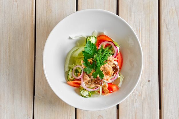 Bovenaanzicht van salade met zalm, tomaat, rode ui en dorblu kaas
