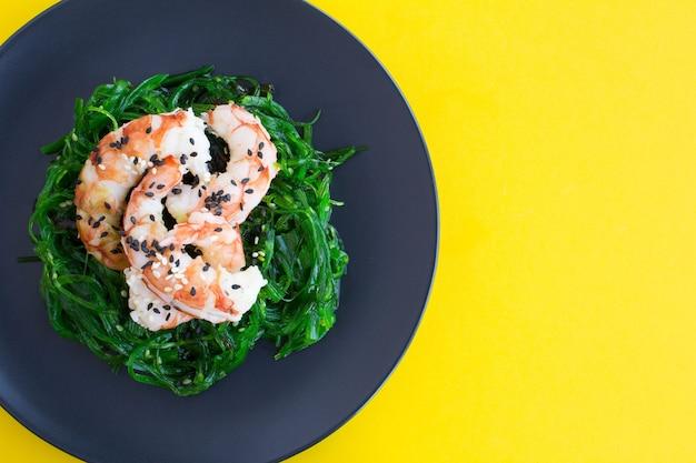 Bovenaanzicht van salade met zeewier en rode garnalen in de zwarte plaat