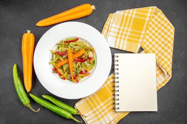 Bovenaanzicht van salade plaat van salade met groenten tafelkleed hete pepers witte notebook