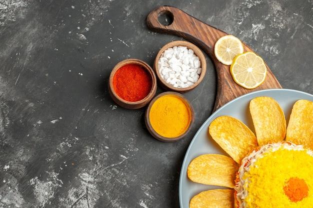 Bovenaanzicht van salade rechtsonder op bordstandaard met citroen en kruiden aan zijkant op donkergrijze tafel