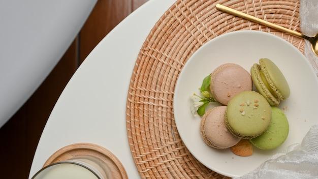 Bovenaanzicht van salontafel met een plaat van franse kleurrijke macarons en een glas melk